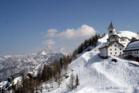 mountain landscape with a church of an abbey on the snow-covered mountain photo