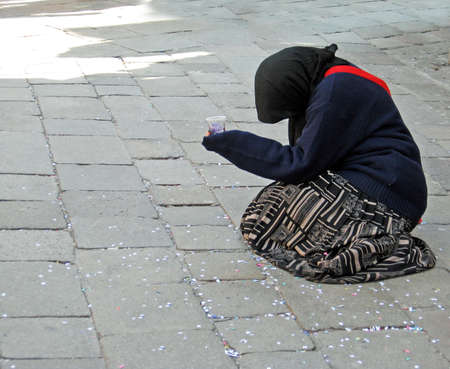 marginalization: beggar asks charity to people in the street  Editorial