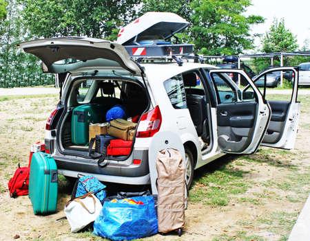 carga: coche de la familia cargado con el equipaje de salir de vacaciones