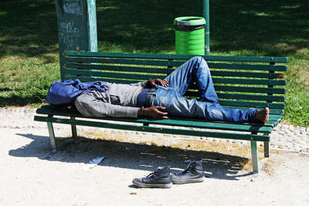 poor marginalized homeless sleeping in a outdoor bench