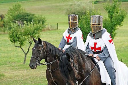 two medieval crusaders shall strutting with their horses blacks in the Italian countryside  photo