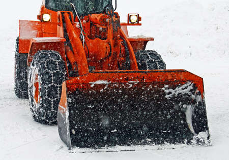 orange snow plow clears the streets during a snow storm in winter photo