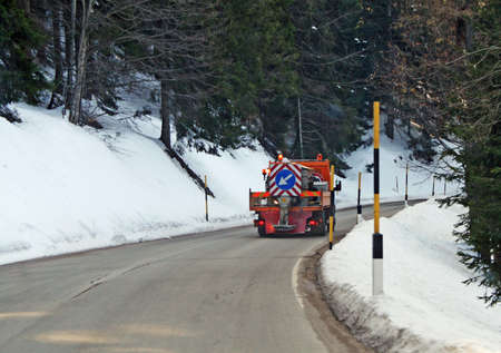 municipal truck with salt spreader system to prevent formation of ice on mountain roads photo
