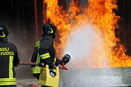 extinguish: Uniformed Firefighters extinguish a fire