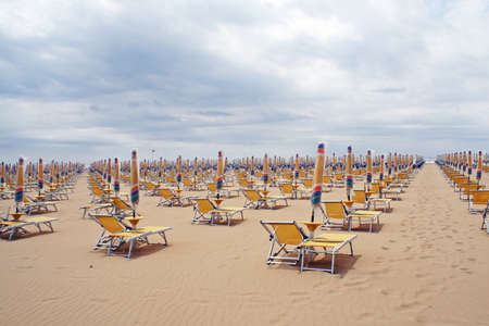 chairs, beach chairs and umbrellas closed in a line along the sandy shore in a day without sunshine photo