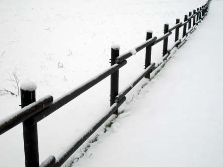 delimit: wood fence covered with white snow in winter in the mountains