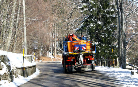 truck with Snowplow and spread salt on the ice