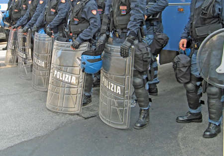 quell: shields of the police on the street in riot gear to quell the unrest