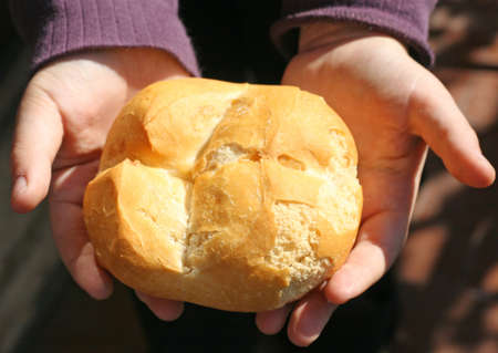 child who breaks a piece of bread with your hands