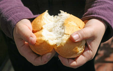 Kind, das ein St�ck Brot bricht mit den H�nden