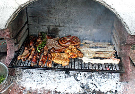 Mixed Grill of meat in the outdoor garden big fireplace