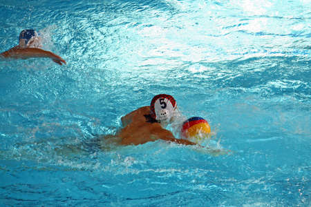 strong swimmers during a game of water polo in the pool