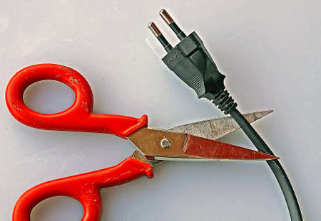 Red handle with scissors that cut the power cord to an electrical outlet photo