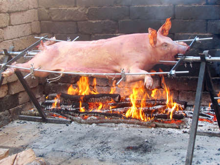 pig roast: good pork is slow cooked over a flame  Stock Photo