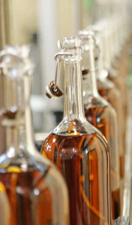 alcohol series: long row of glass bottles capped in a bottling factory