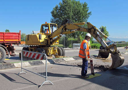 roadworks with a yellow scraper to work in the middle of the road photo