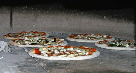 woodfired: pizza with mozzarella and tomato sauce in baking in a wood-fired oven Stock Photo