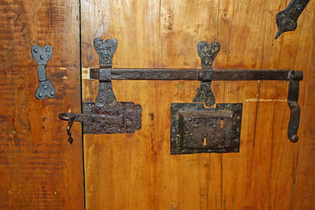 deadbolt: old iron with deadbolt lock to close the heavy wood door Stock Photo