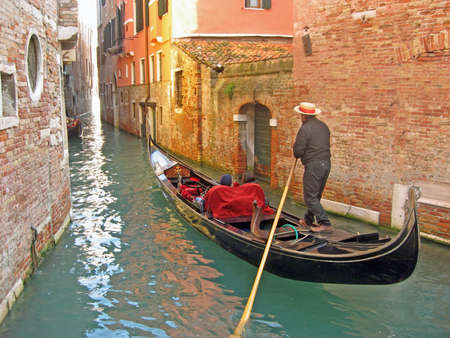 gondolier in a gondola along a canal through the houses of Venice photo