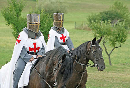 two medieval crusaders shall strutting with their horses blacks Stock Photo