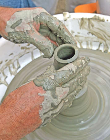 craftsman shapes a vase of clay on the wheel photo