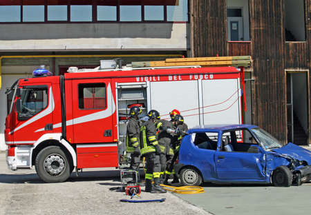 blue car destroyed in a traffic accident and trucks of firefighter