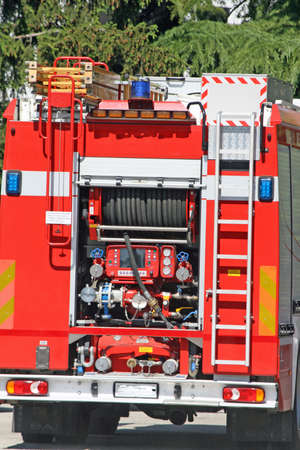 pumper: pump and pipe truck of firemen in action with sirens flashing blue
