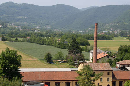 brick kiln: large brick chimney of a furnace and the hills with homes