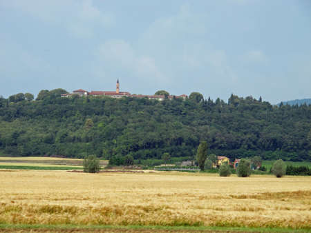theological: ancient abbey on a hill and the field of wheat Stock Photo