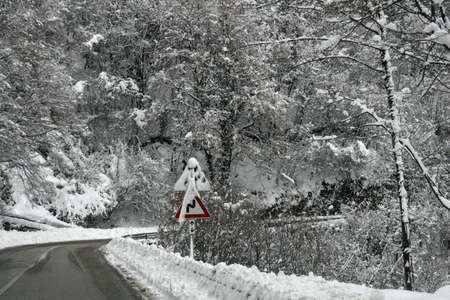 Iced road full of snow with sign of attention in winter photo