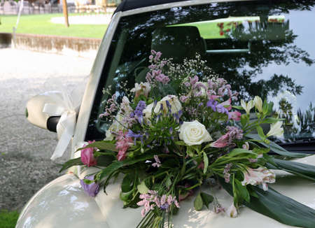 Bouquet of flowers and bouquets on the hood of the car of the newlyweds photo