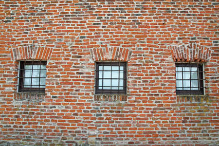lattice window: red brick wall with iron lattice window of an ancient prison Stock Photo
