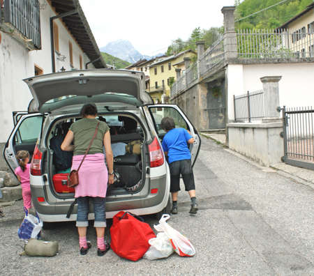 Family car ready to go with the trunk full of suitcases and bags with kids