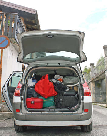 Family car ready to go with the trunk full of suitcases and bags photo