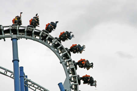 baskets and trolleys with frightened people hung in a track of a roller coaster