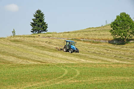 farmer and tractor while cutting grass in a meadow in the mountains Stock Photo - 14405803