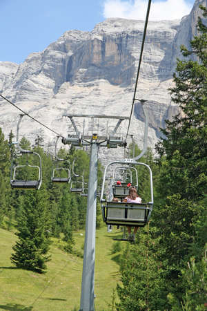 Chair lift people up towards the top of the Dolomites in alta badia Stock Photo - 15015961
