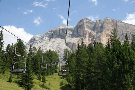 chairlift: Chair lift people up towards the top of the Dolomites in alta badia