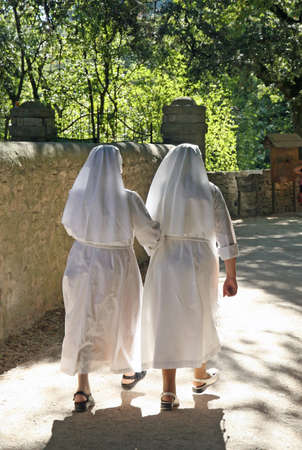 petticoat: two nuns dressed in white walk along the path of the sanctuary Stock Photo