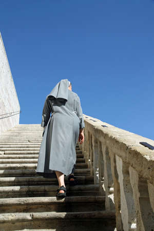petticoat: un with grey dress that goes up the stairs of the sanctuary Stock Photo