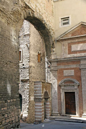 etruscan: ancient Etruscan arch made of lime and brick between the medieval houses Stock Photo