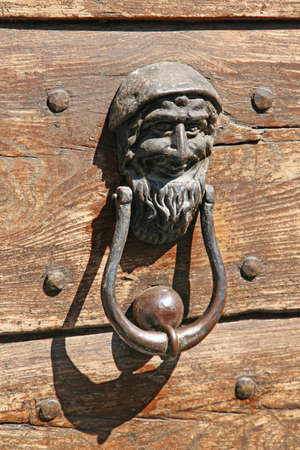 iron door knockers with one face to knock on the wooden door photo