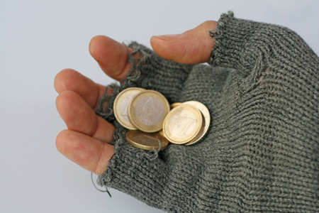 a poor man collects alms from a Euros in his glove photo