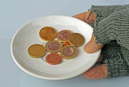 hombre pobre: platillo blanco con las monedas dentro en manos de un hombre pobre Foto de archivo