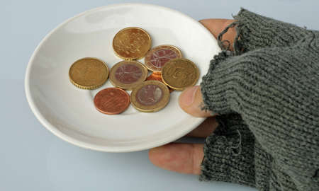 dish with coins inside held by a poor man photo