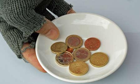 mano guantata di un povero e piattino con alcune monete