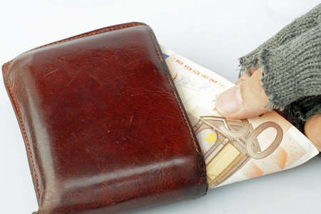 marginalized: hand of a poor man who steals money from a wallet Stock Photo