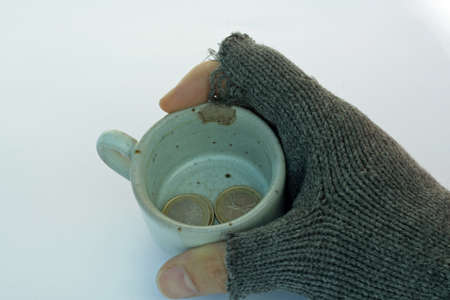 almsgiving: hand of a poor man holding a cup of almsgiving with coins