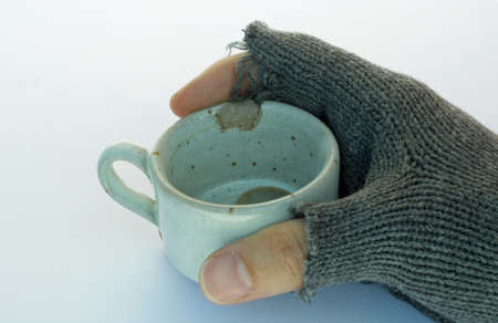 hand of a poor man holding a cup of coffee with coins photo