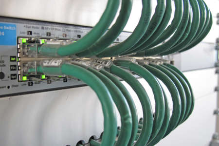 data transmission: Green computer network cable in a rack of data processing center